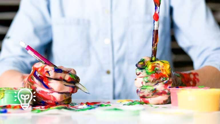 Hände halten Stift und Pinsel (Symbolfoto phaydon Marktforschung Lösungen)