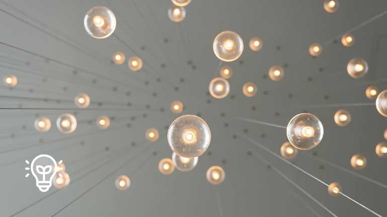 Vielzahl hängender Glühbirnen (Symbolfoto phaydon Marktforschung Lösungen)