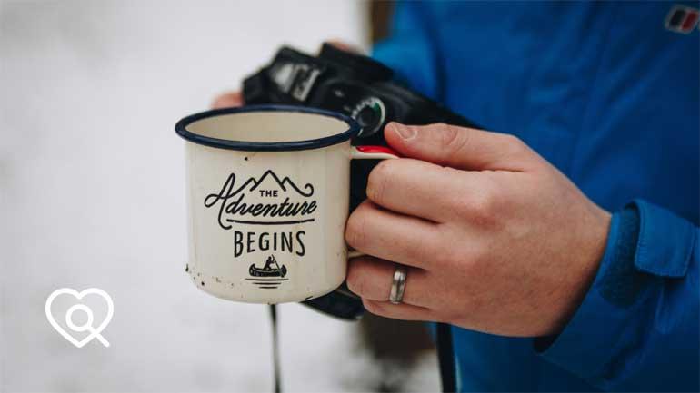 Hand hält Kaffeetasse mit der Aufschrift 'The Adventure Begins' (Symbolfoto phaydon Marktforschung Lösungen)