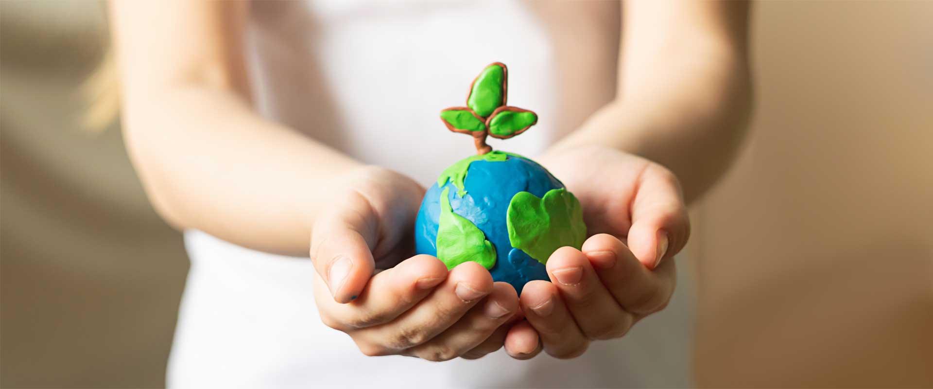 Kind hält Weltkugel aus Knete in den Händen