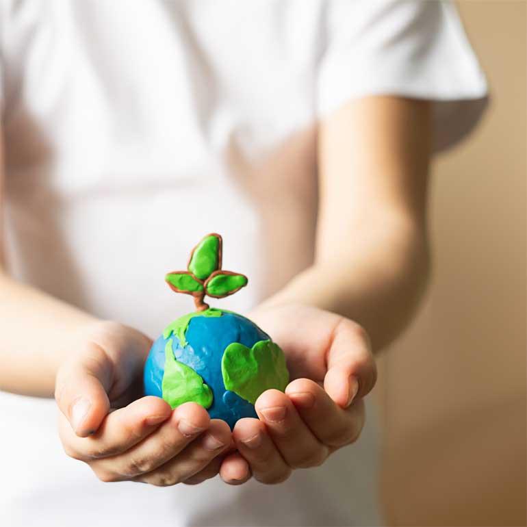 Kind hält Weltkugel aus Knete in den Händen - Motiv zu einer Marktforschungsstudie